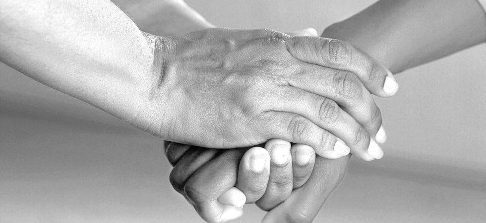 Hände halten einander in der Sellsorge.