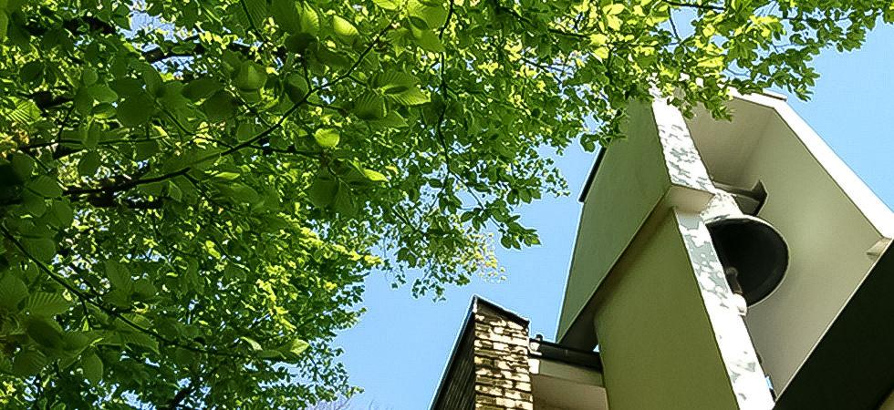 Glockenturm in der Sonne mit Baumkrone